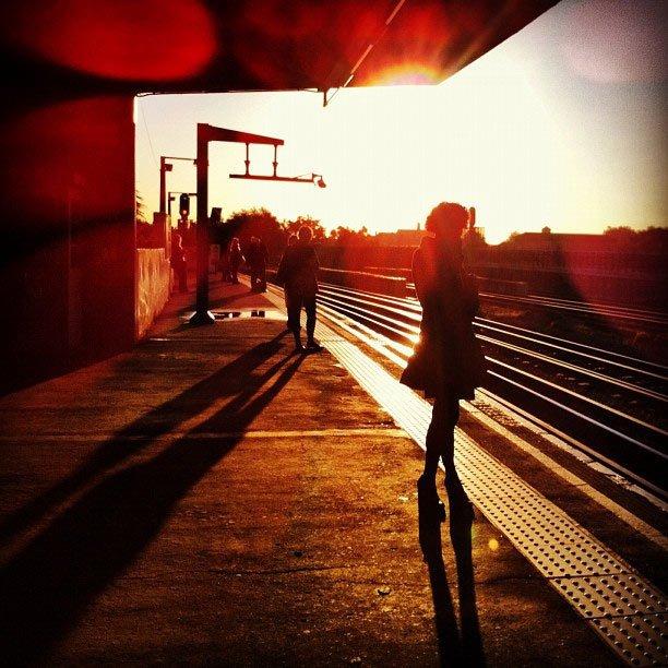 photo d une femme sur un quai avec un coucher de soleil